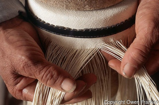 June 1995, Pile, Ecuador --- Raul Alarcon Holguin weaves a Montecristi Fino Panama hat as he bends over a weaving stand, placing his chest on wooden blocks. He is using stripped and dried paja toquillo palm fronds to create a fine weave. --- Image by © Owen Franken/CORBIS